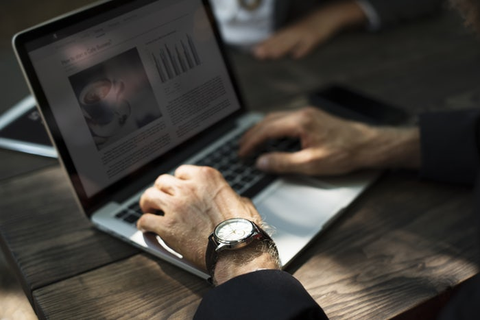 Business man using online marketing strategies from laptop