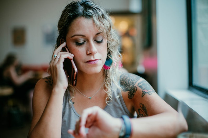 A woman looking at her watch while on the phone, showing she doesn't have the time for phone calls