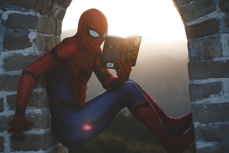 Spiderman reading a story — presumably about business blog post ideas